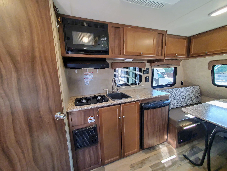 Kitchen with 2 burner stove, hood/microwave, sink, and fridge.. Coachmen Viking 14R 2018