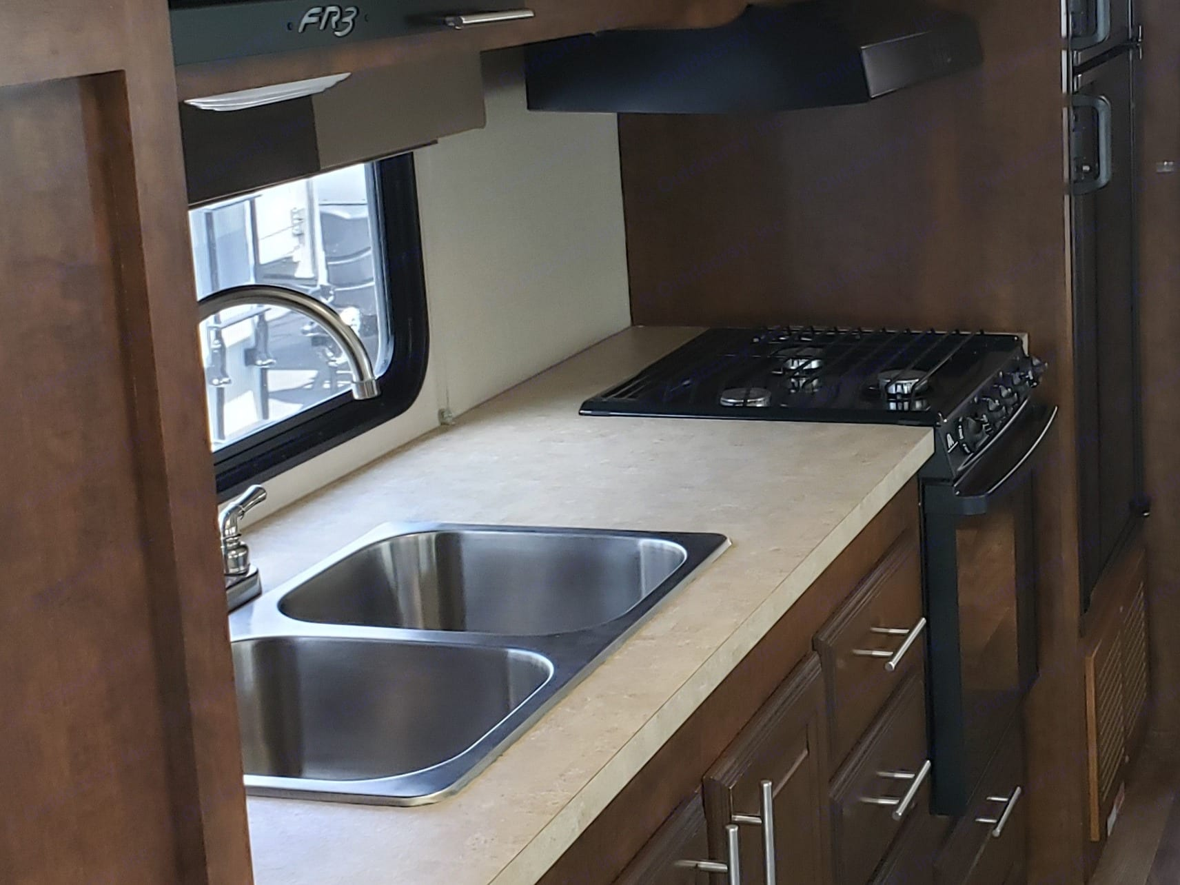 """Large counter area with double stainless steel sinks, with large refrigerator microwave,  32"""" tv, stove top with large oven.. Forest River Fr3 2015"""