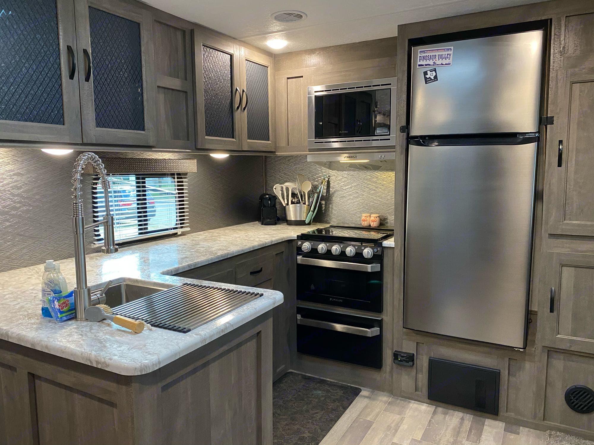 large, spacious kitchen - 3 burner stove, oven, microwave, large freezer/fridge. Forest River Vibe 2020