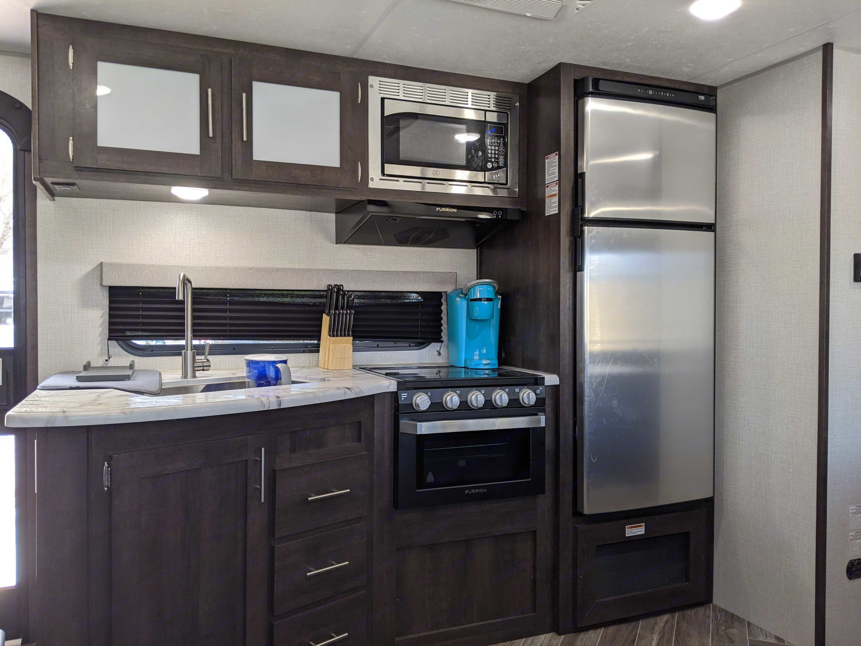 Kitchen - full kitchen that include dishes, silverware, knives, water pitcher, Keurig, and much more. K-Z Manufacturing Sportsmen 2020