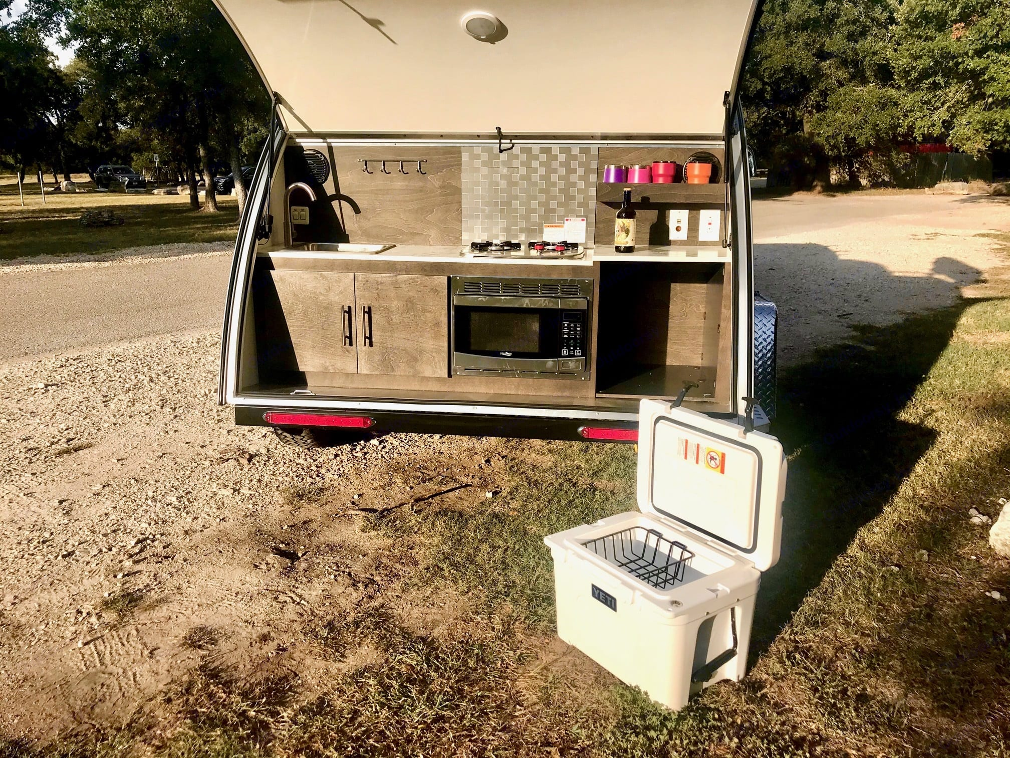 The hatch of the camper lifts up to display a full kitchen with a sink, microwave, two propane burners and a Yeti cooler.. Nucamp T@G XL Boondock 2021