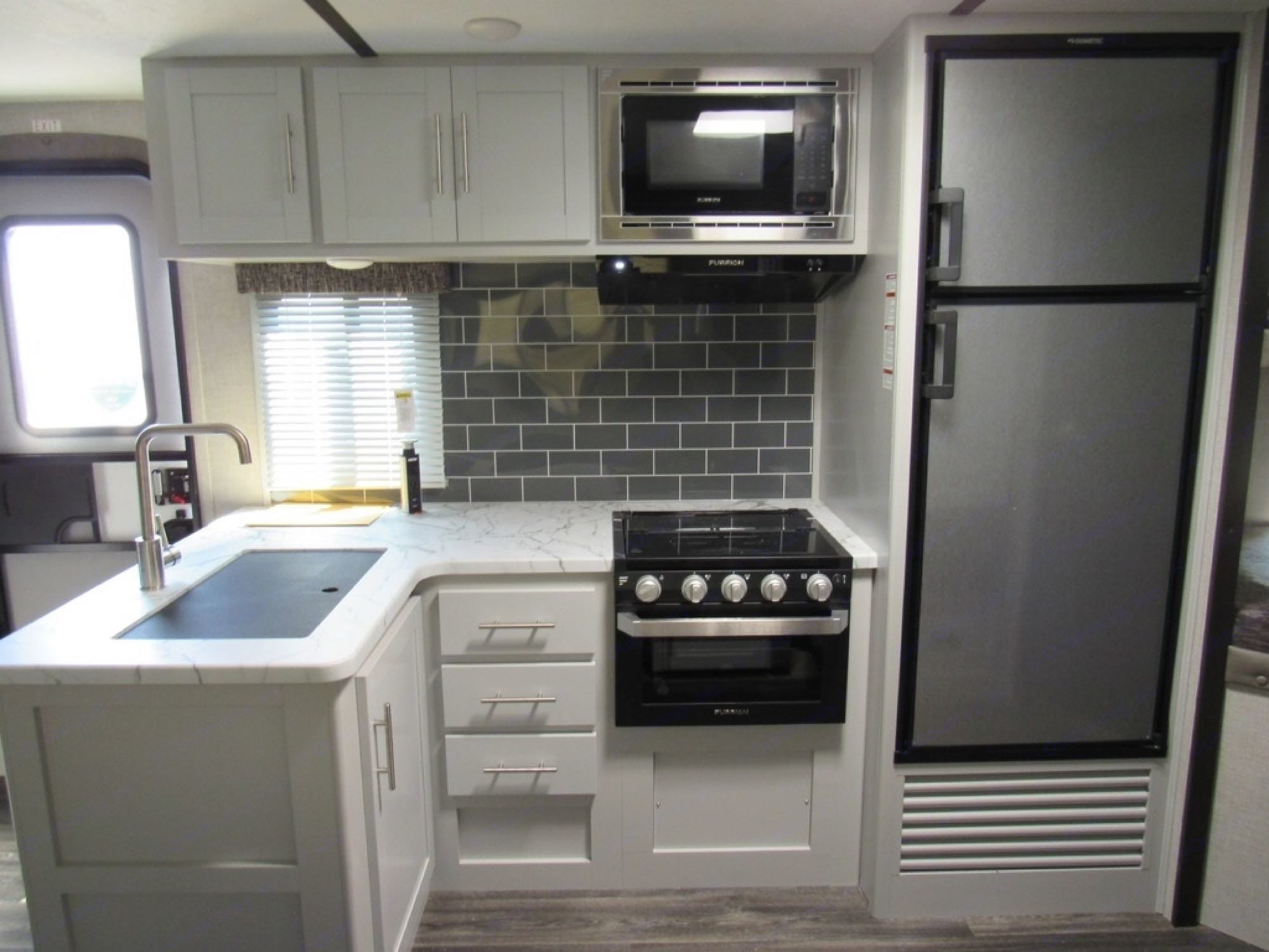 Large Stainless sink with cover for more counter prep space. Oven and 4 burner gas stovetop.  Microwave as well. . Keystone Bullet 243BHS 2021
