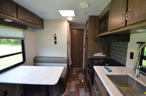 Full kitchen includes gas stove, oven, microwave, deep sink and plenty of storage space. East to West Silver Lake 27 KNS 2021