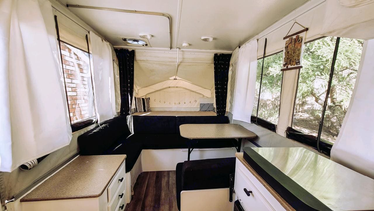 inside view w Dinette open/ Full size bed at end-drawers on left hand side and hidden toilet under bench seat.. Forest River Rockwood Freedom 2011