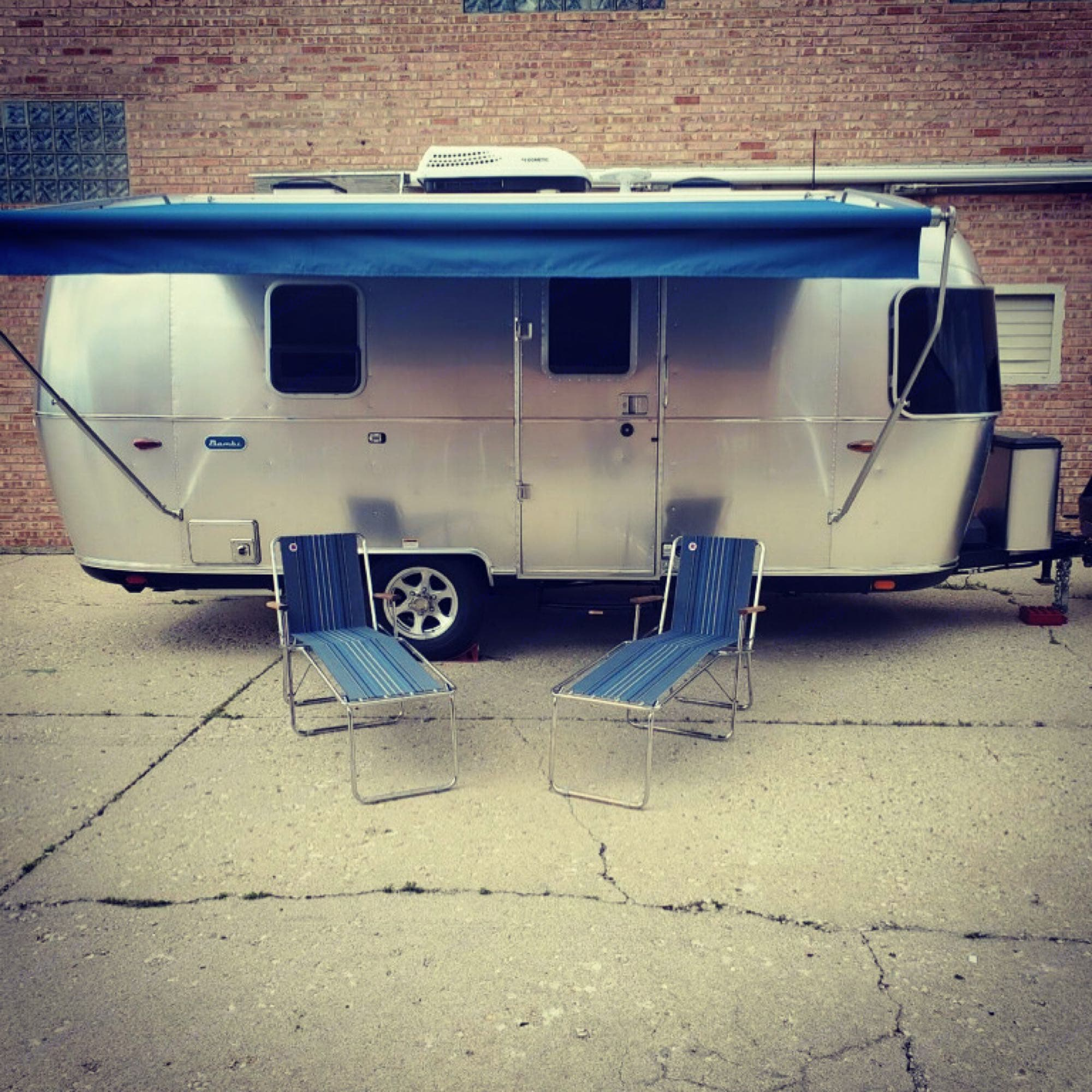 """Upgraded blue ZipDee awning with matching custom ZipDee new """"vintage"""" folding chairs with lounge attachments!. Airstream Bambi 2020"""