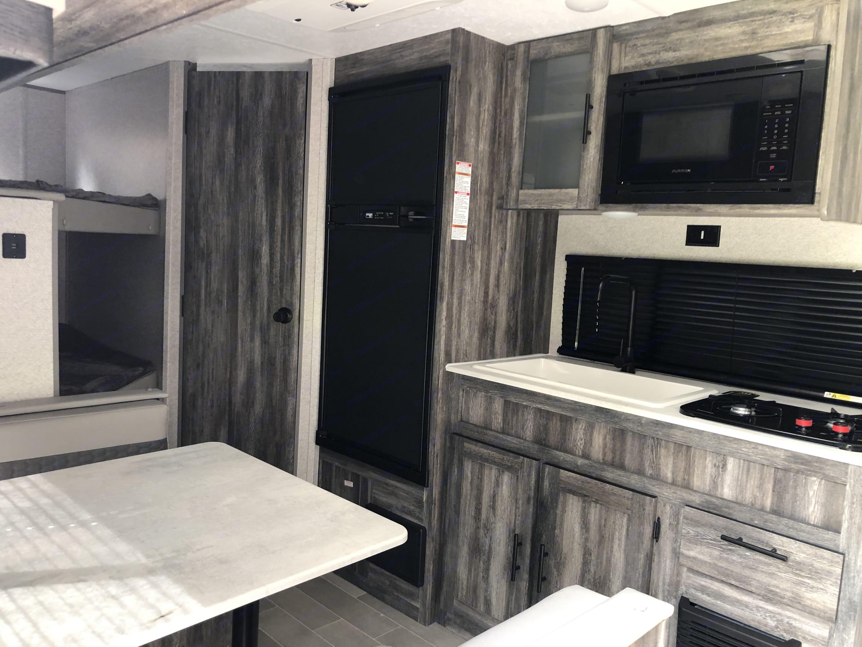 Fridge/freezer, kitchen sink and stovetop, microwave, bathroom door. Forest River Wildwood 2021