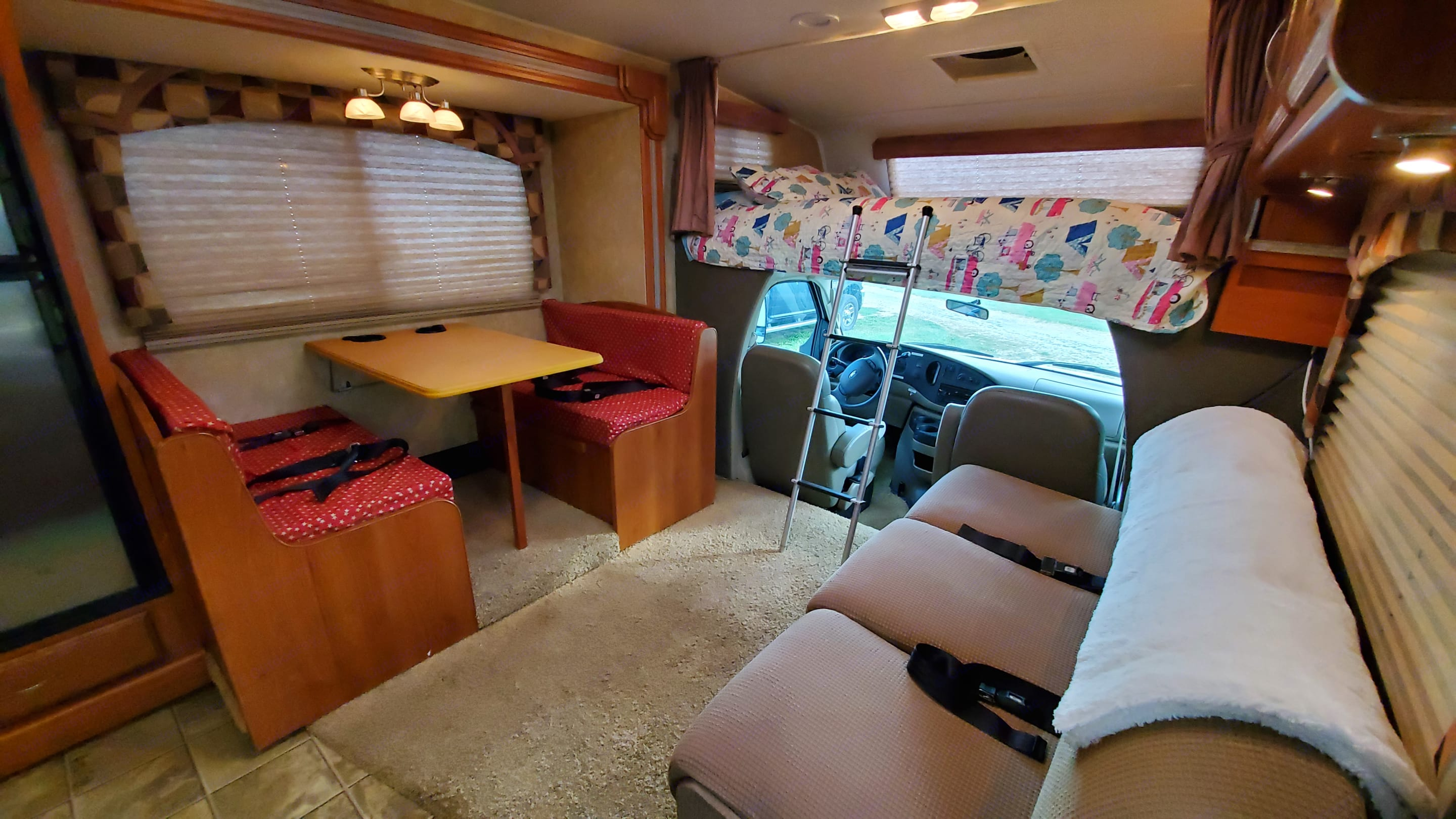 Living room with blinds closed and slide out. Bunk with TV that pulls out to view from living area. Coachmen Leprechaun 2008