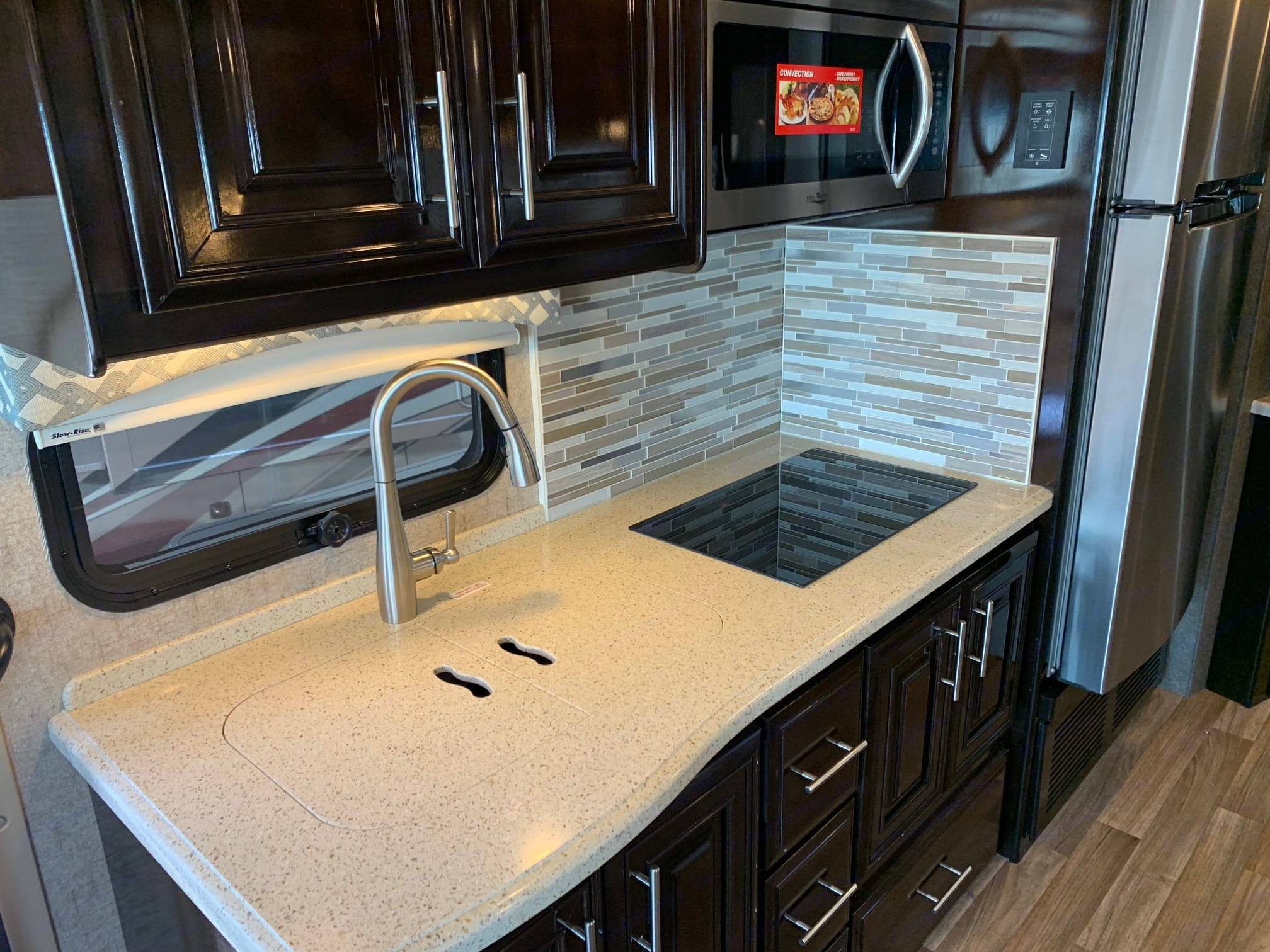 Kitchen area- Sink, convection oven/microwave and induction stovetop. Thor Motor Coach Miramar 2019