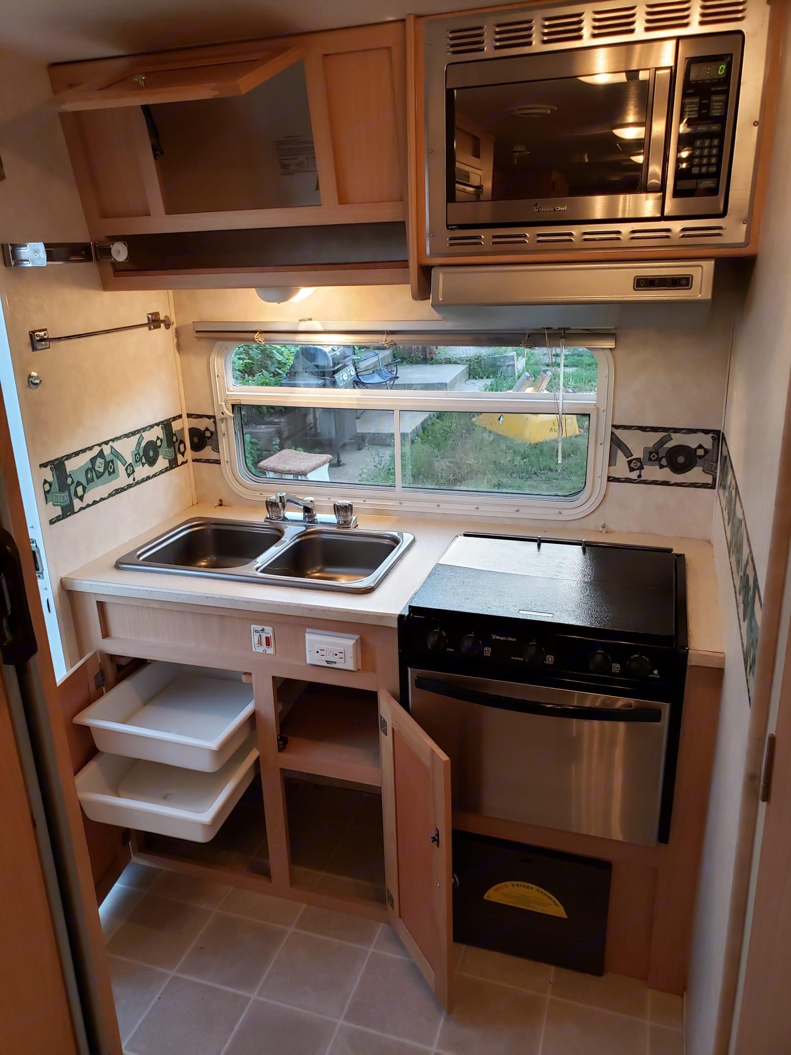 Kitchen w/ cabinets open. Forest River Surveyor 2006