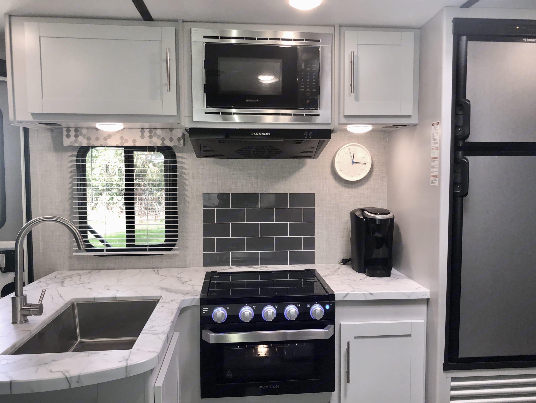 Modern Kitchen with stainless steel sink, pans, utensils, plates, bowls, flatware set, coffee machine, toaster, etc. Keystone Bullet 2020