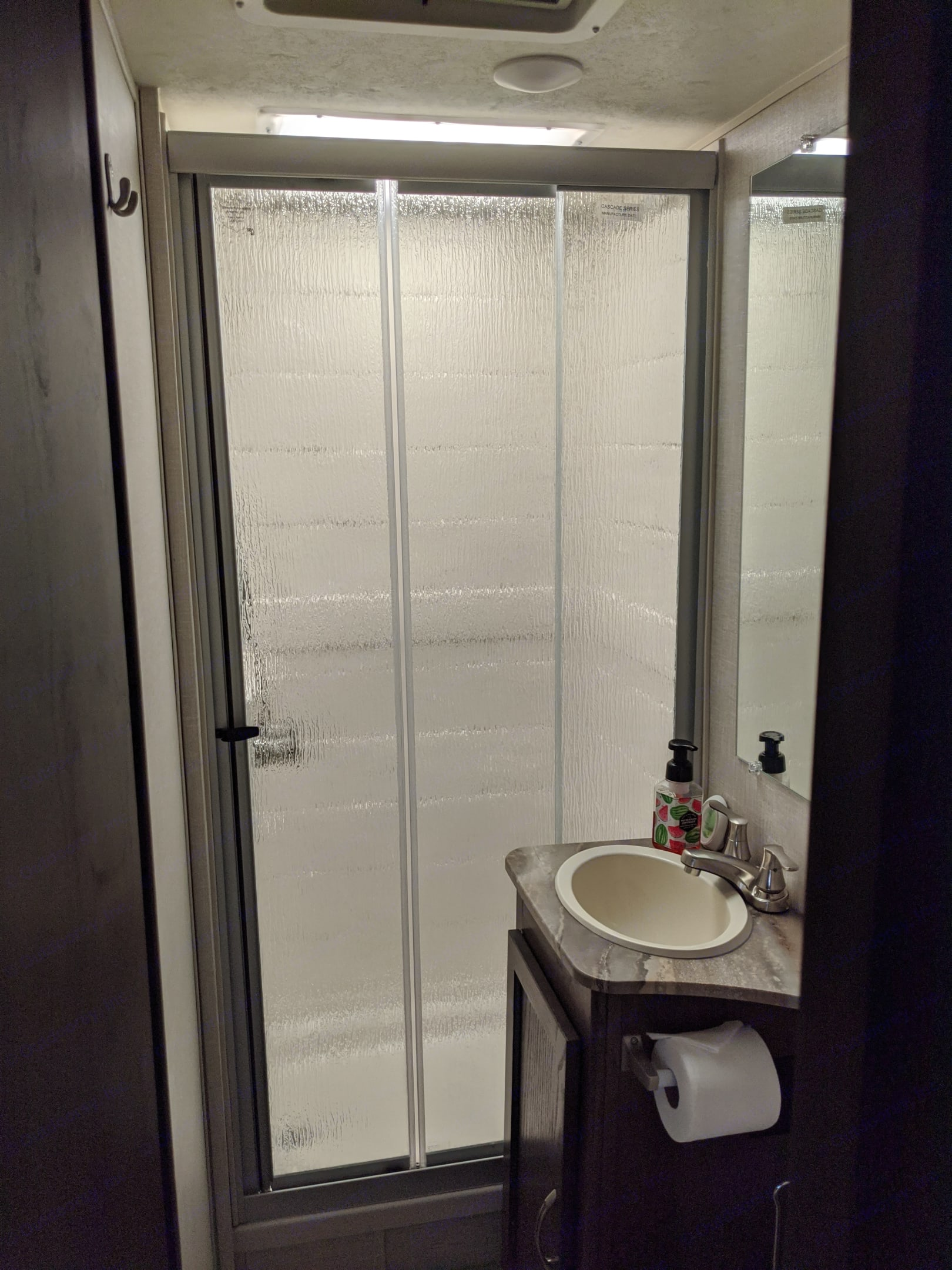 Bathroom with vanity, sink and shower with sliding glass doors. Coachmen Freelander 2020