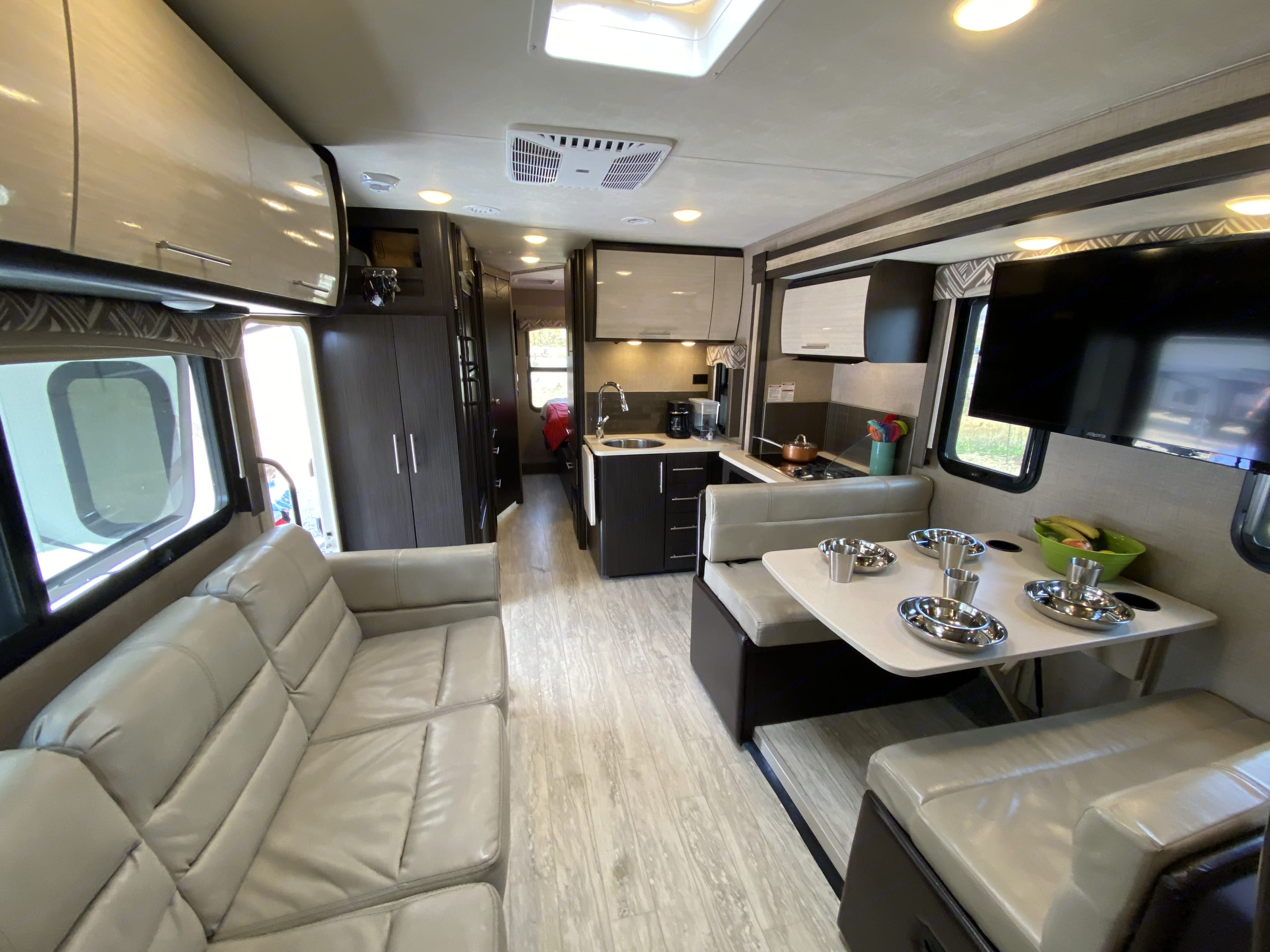 Large living space with couch in front of large TV above dinette space.. Thor Motor Coach Axis 2019