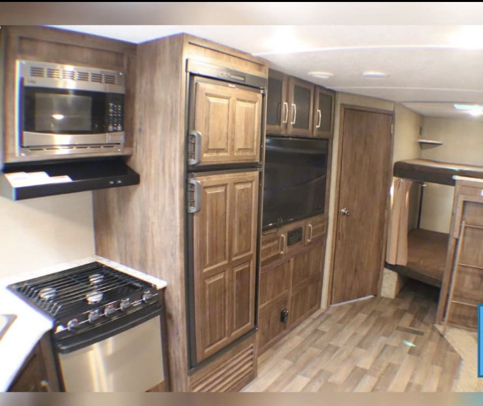 Full kitchen, refrigerator and living area with large TV. Bluetooth compatible with exterior speakers.. Keystone Cougar 2018