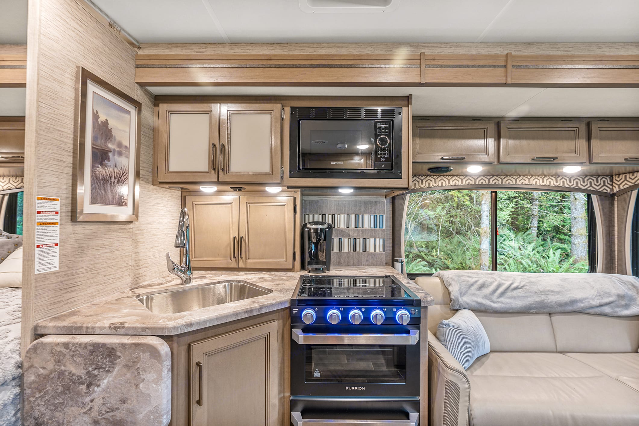 """Kitchen on """"off camp"""" side w/ extendable counterspace, wine rack, oven, micro and burners. Thor Motor Coach Chateau 27R 2021"""