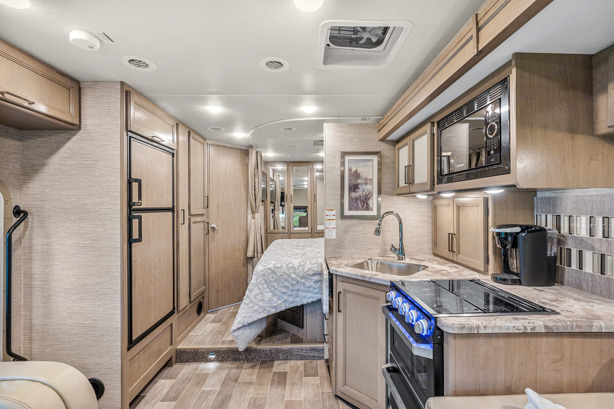 View of fridge, freezer and loads of storage with pull out drawers. Thor Motor Coach Chateau 27R 2021