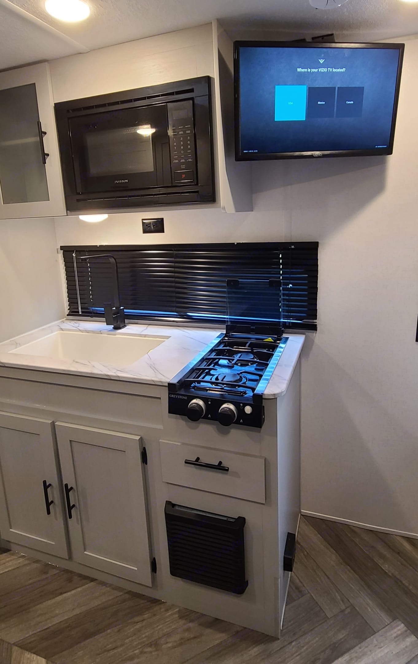 Microwave and stove with large window behind sink. Forest River Salem 2021