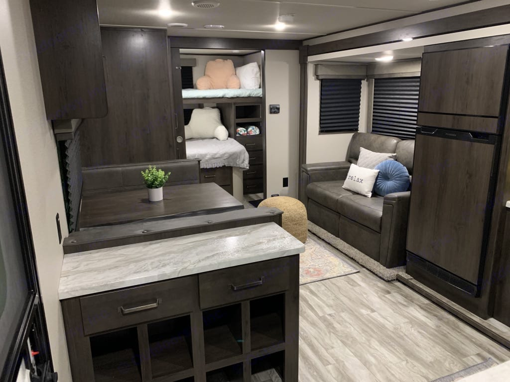 View of main living space with conversational seating with dinette located across from couch and bin for easy shoe organization.. Grand Design Other 2021