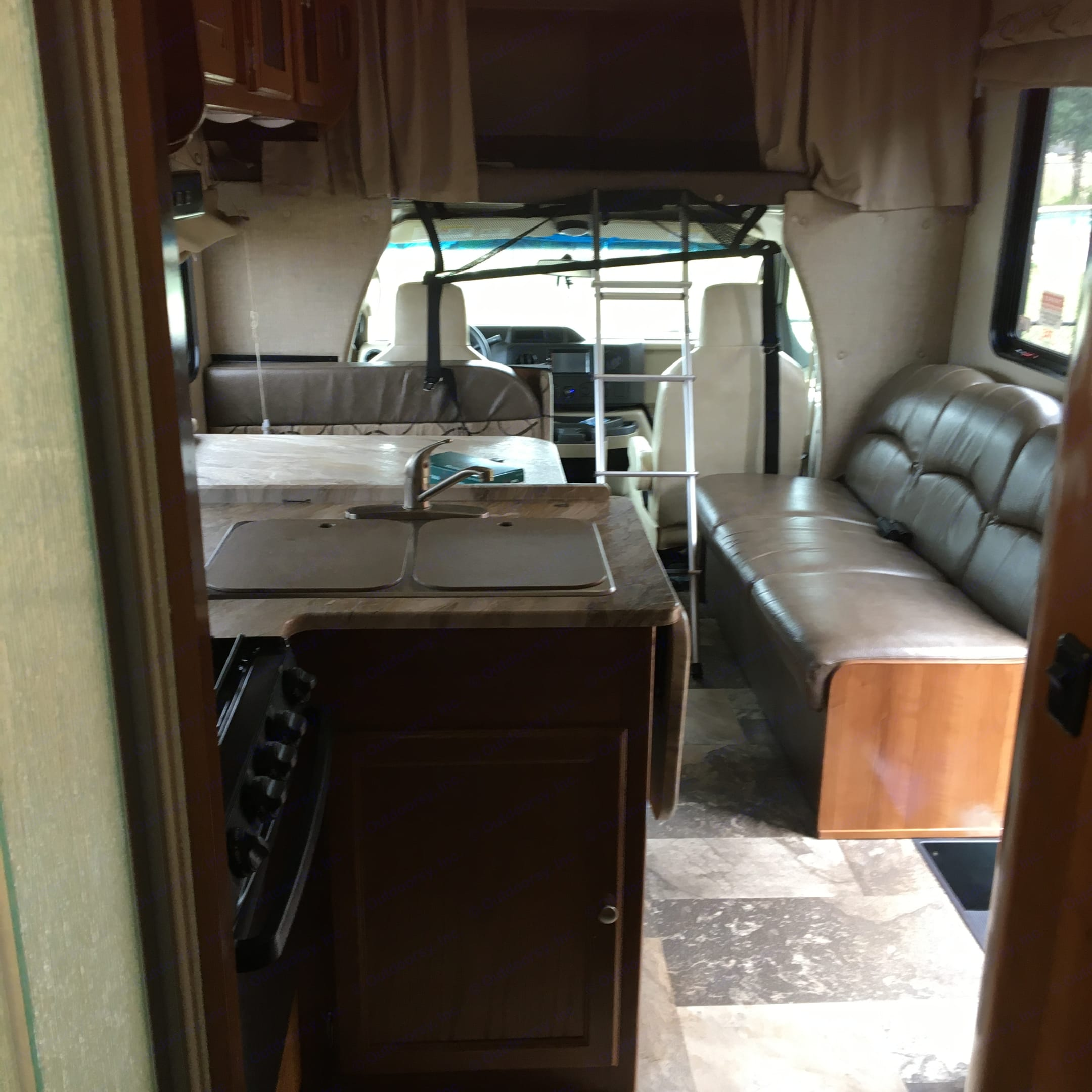 Back to front view of kitchen, dinning, couch, and driver cabin.. Coachmen Leprechaun 2019