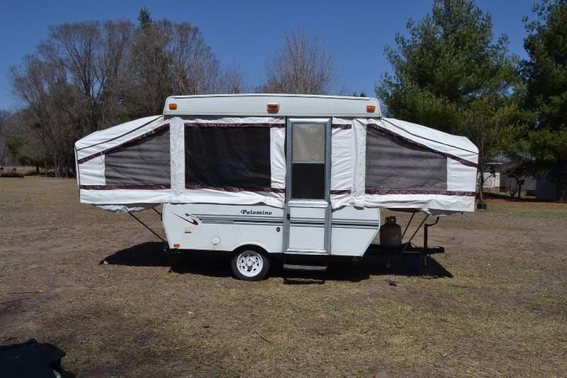 Travel trailer is fully opened and extended with the two sleeping areas on each side of the unit visible.. Palomino Pinto 1992
