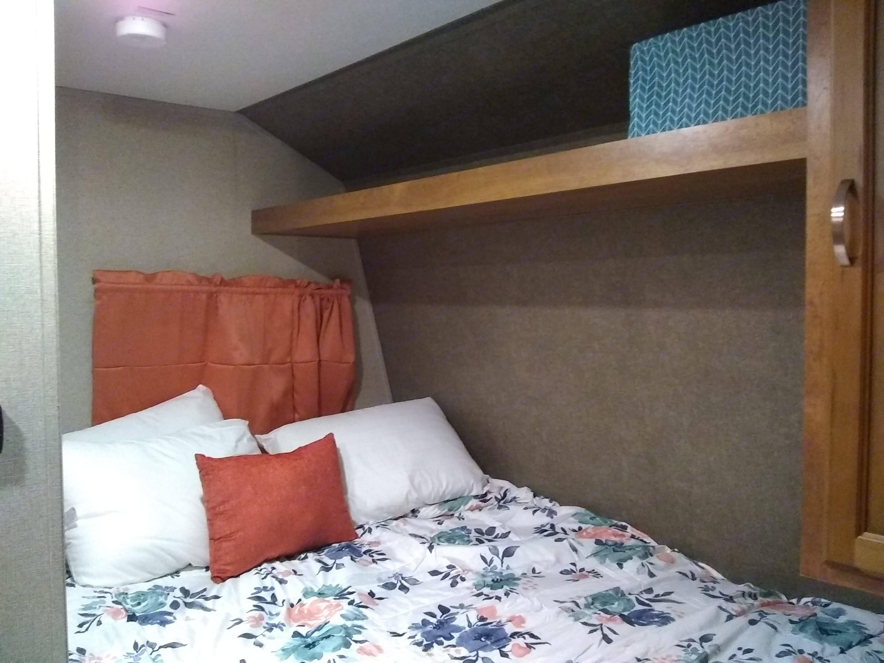 Queen bed with shelf above. Forest River Springdale 2017