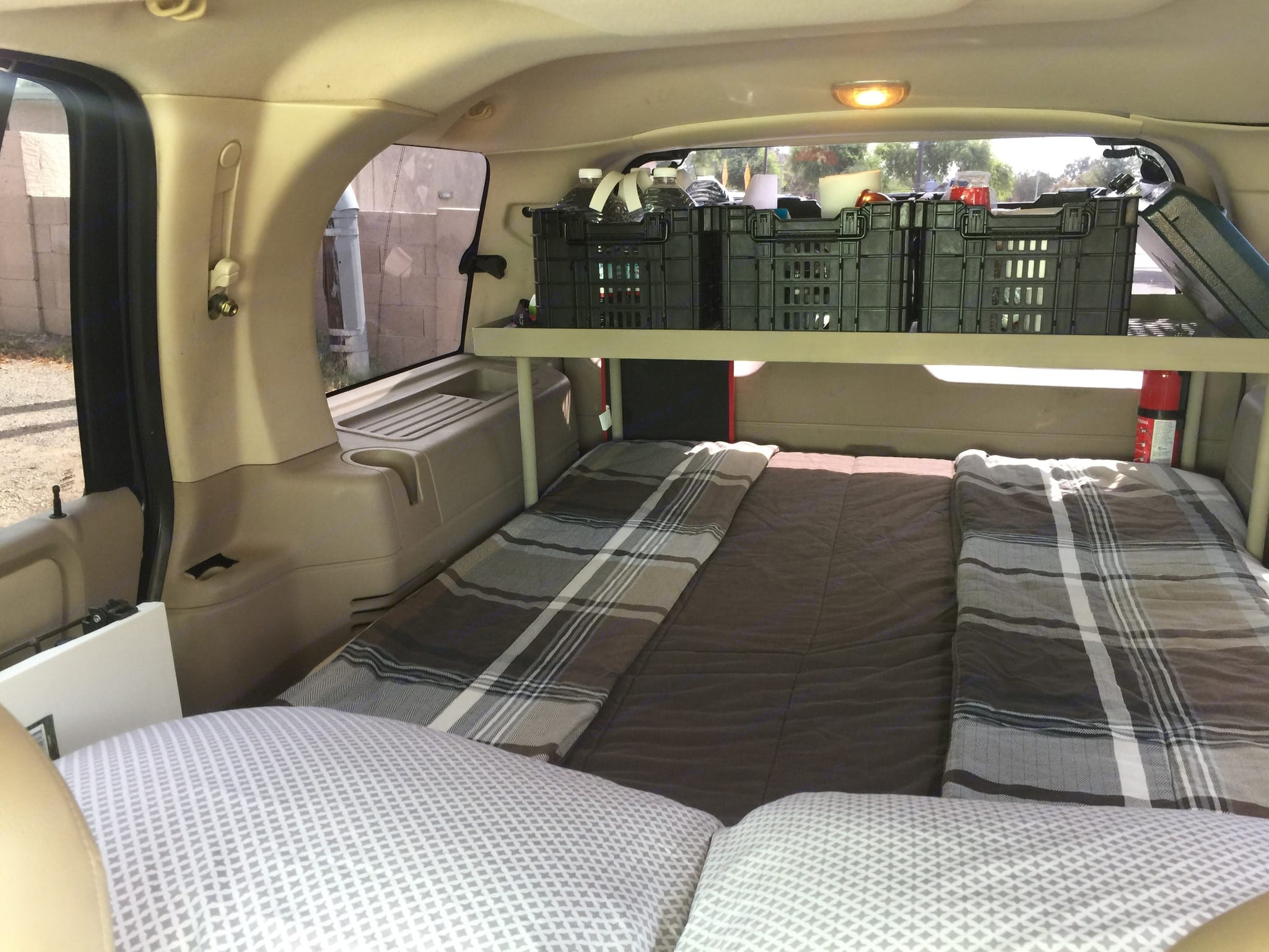 """Comfy memory-foam mattress with soft sheets and blankets...WAY better than sleeping bags, and if it's too cold or wet to be outside...roll up the windows and sleep soundly indoors. The bed measures 50"""" wide x 80"""" long (Queen length, double width). Ford Campervan Expedition Adventure 4x4 Camper Van Conversion 2005"""