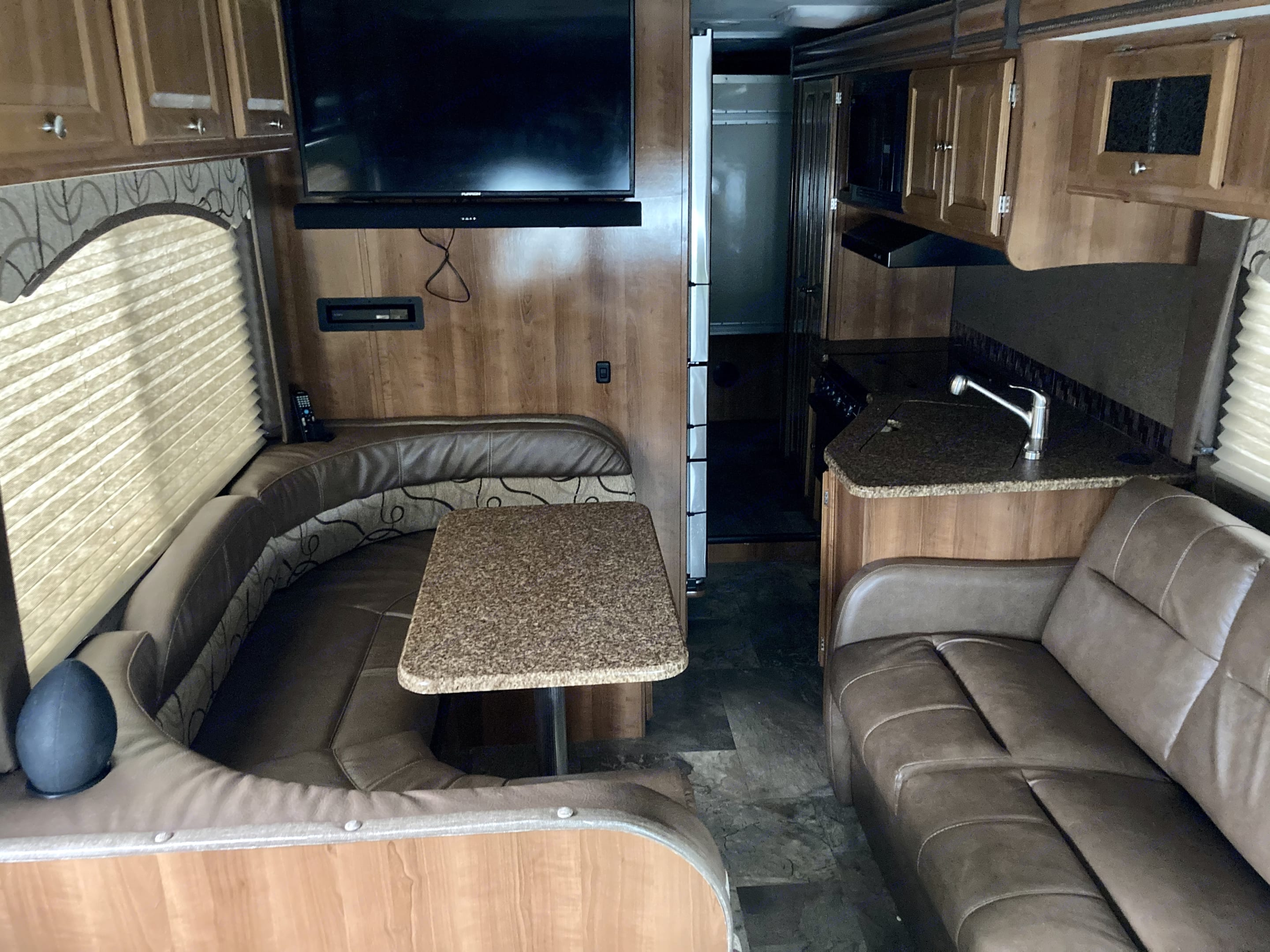 Kitchen with full sized refrigerator and living space . Coachmen Leprechaun 2018