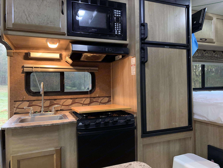 Full kitchen with microwave, gas stove, gas oven, fridge, and freezer. Coachmen Freelander 2014