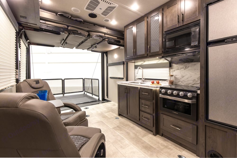 View of kitchen, sitting and patio. Dining and loft bed in up position.. Grand Design Momentum 2020