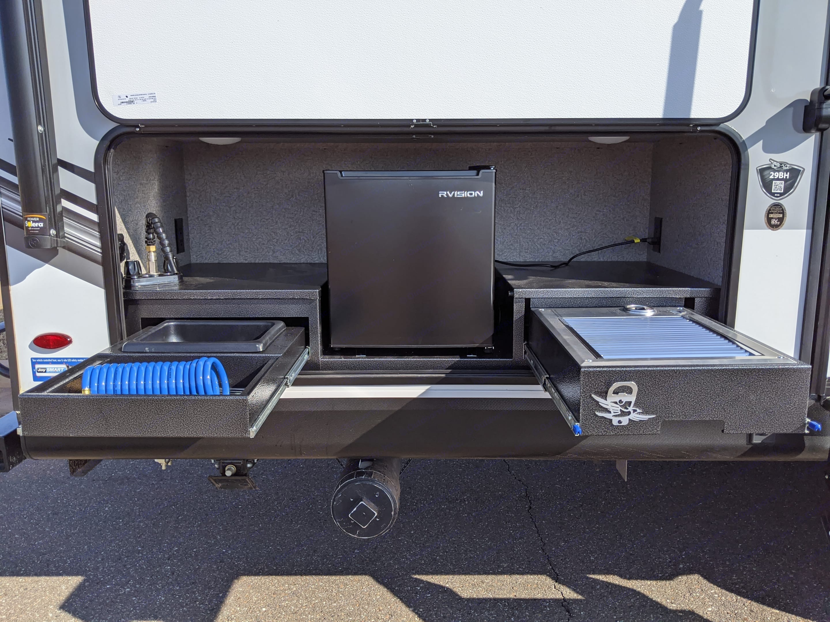 Outdoor Kitchen with stainless steel grill, refrigerator, and sink.. Jayco White Hawk 2021