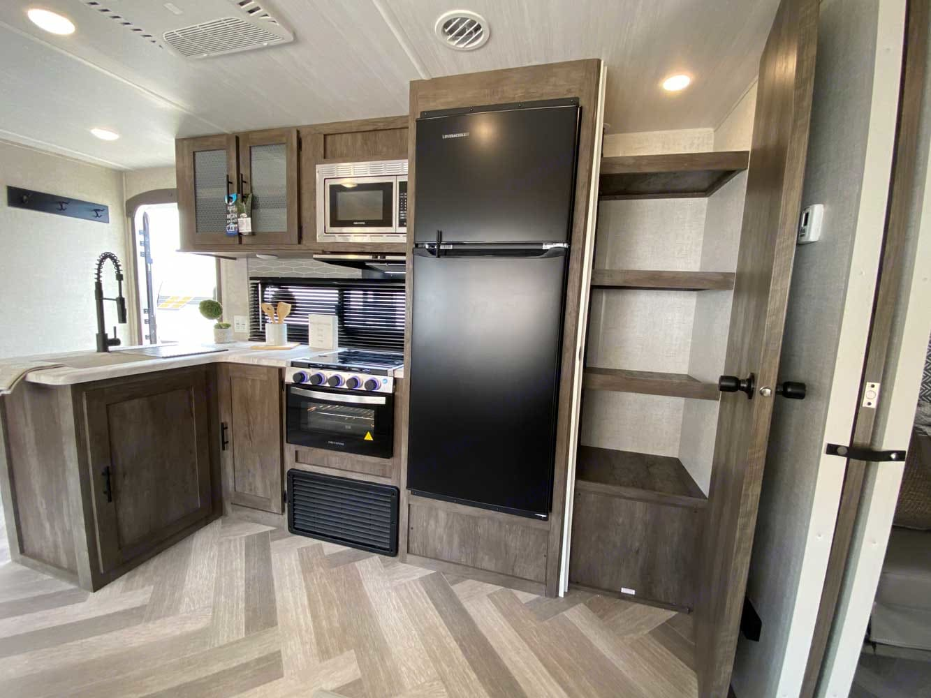 Kitchen complete with fridge.  Kitchen is fully stocked with pots, pans, utensils, baking sheets, plastic cups, paper plates, etc.. Forest River Salem 2021