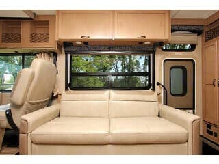 View of convertible sofa and doorway. Thor Motor Coach A.C.E 2018