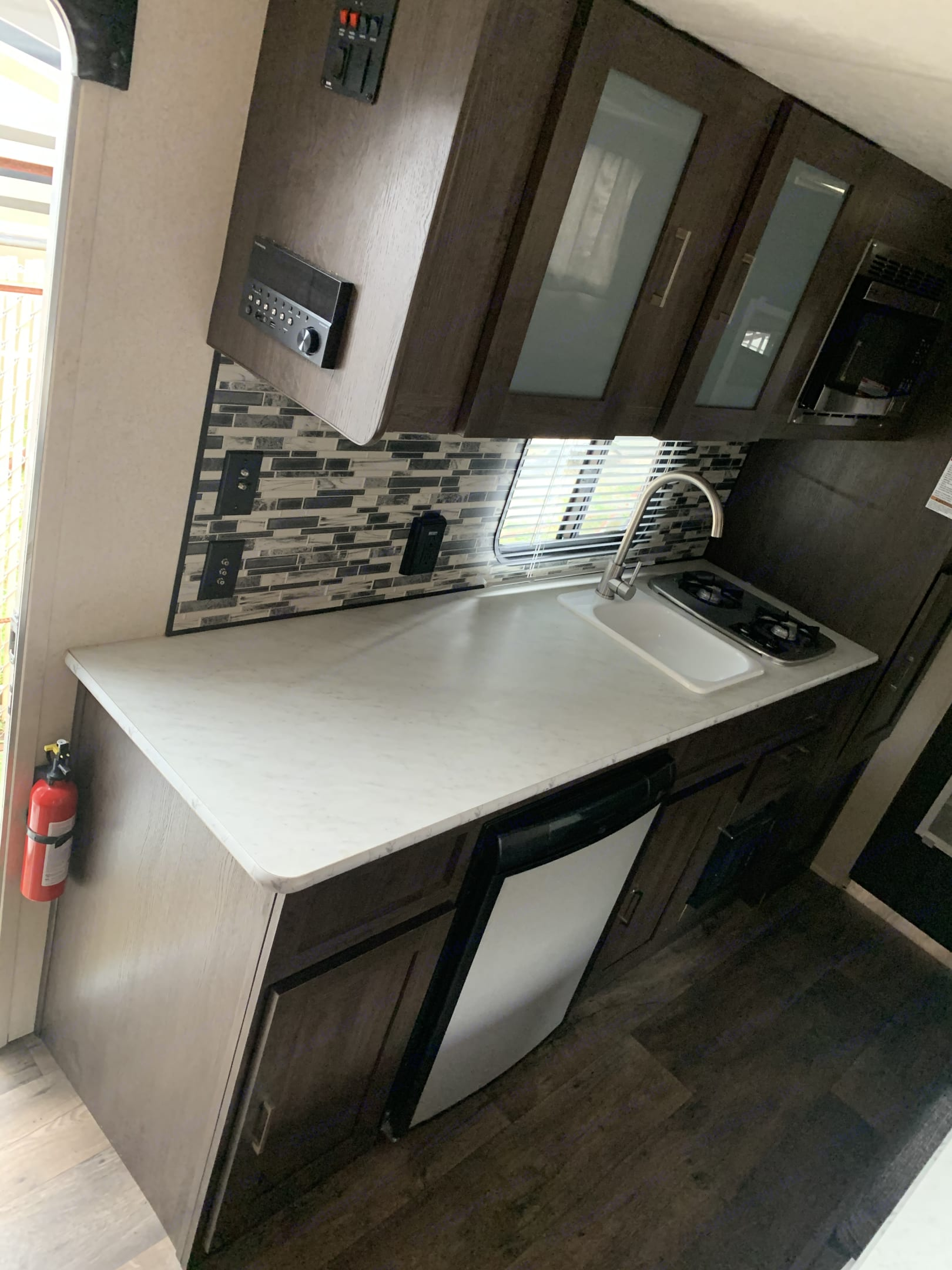 fully stocked kitchen with fridge, stove, and microwave. Forest River Wildwood X-Lite 2018