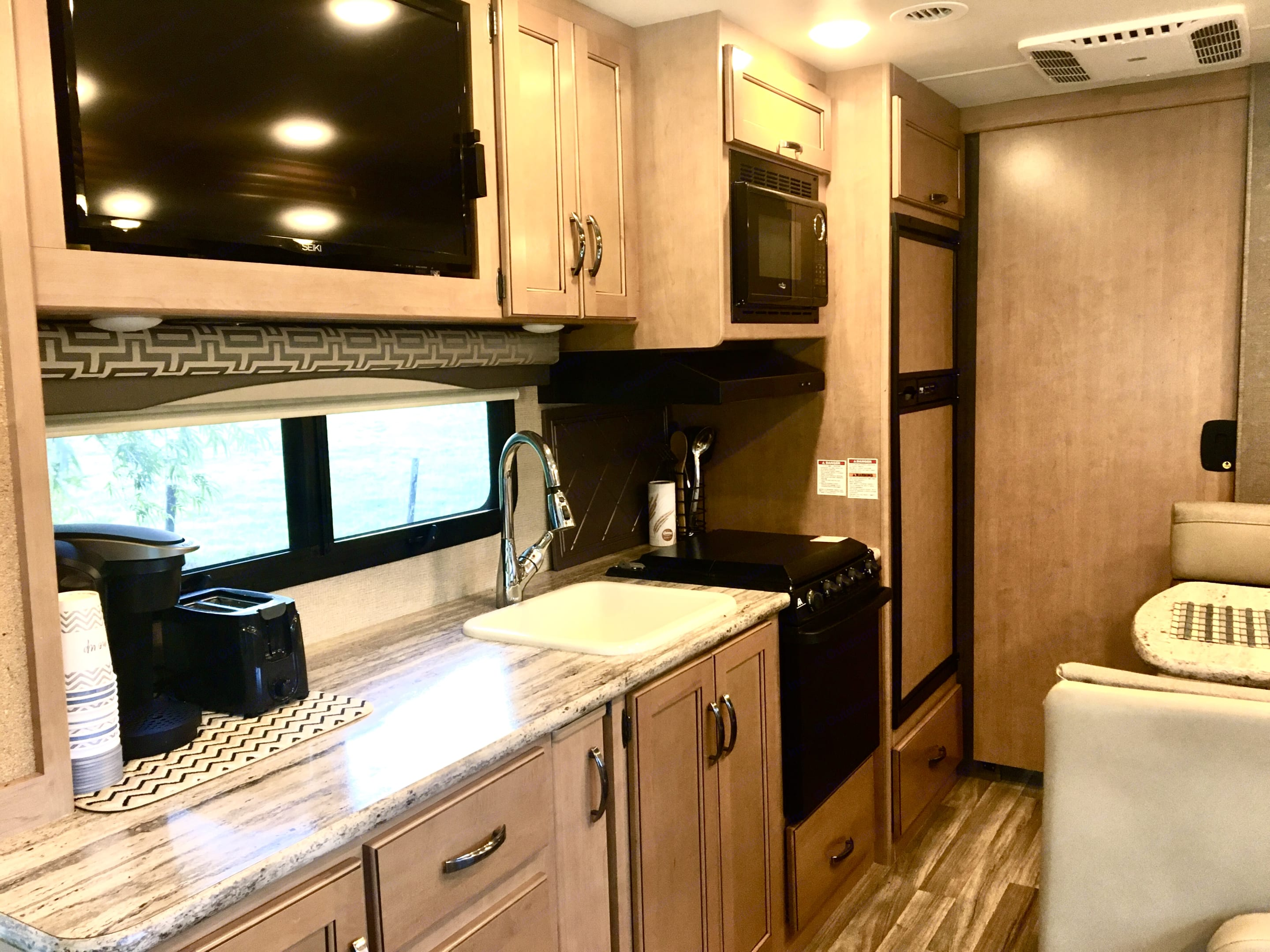 Our RV comes with a medium sized refrigerator, freezer, three-burner stove, oven, microwave, coffee maker, and a toaster. The living area has a TV.. Thor Motor Coach A.C.E 2017