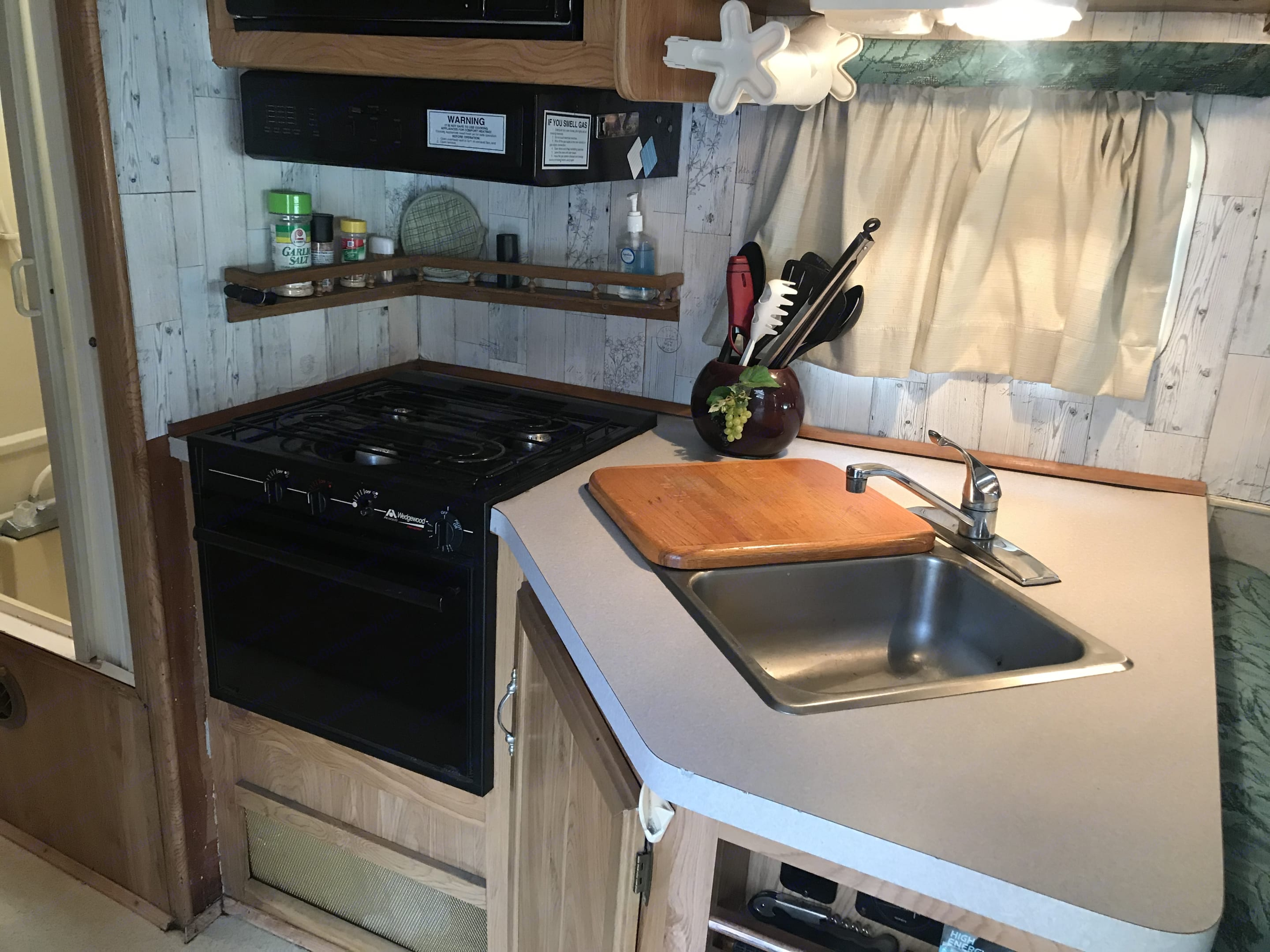 Here's the kitchen showing double sinks, cutting board, 3-burner stove, oven, vent, window, and microwave (above the vent).. Ford Fourwinds 1994
