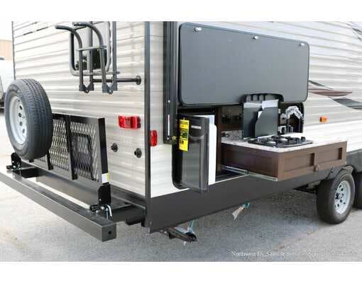 Stand under the awning and cook breakfast, lunch or dinner on the outdoor kitchen that features 2 burners, sink and refrigerator.. K-Z Manufacturing Sportsmen 2019