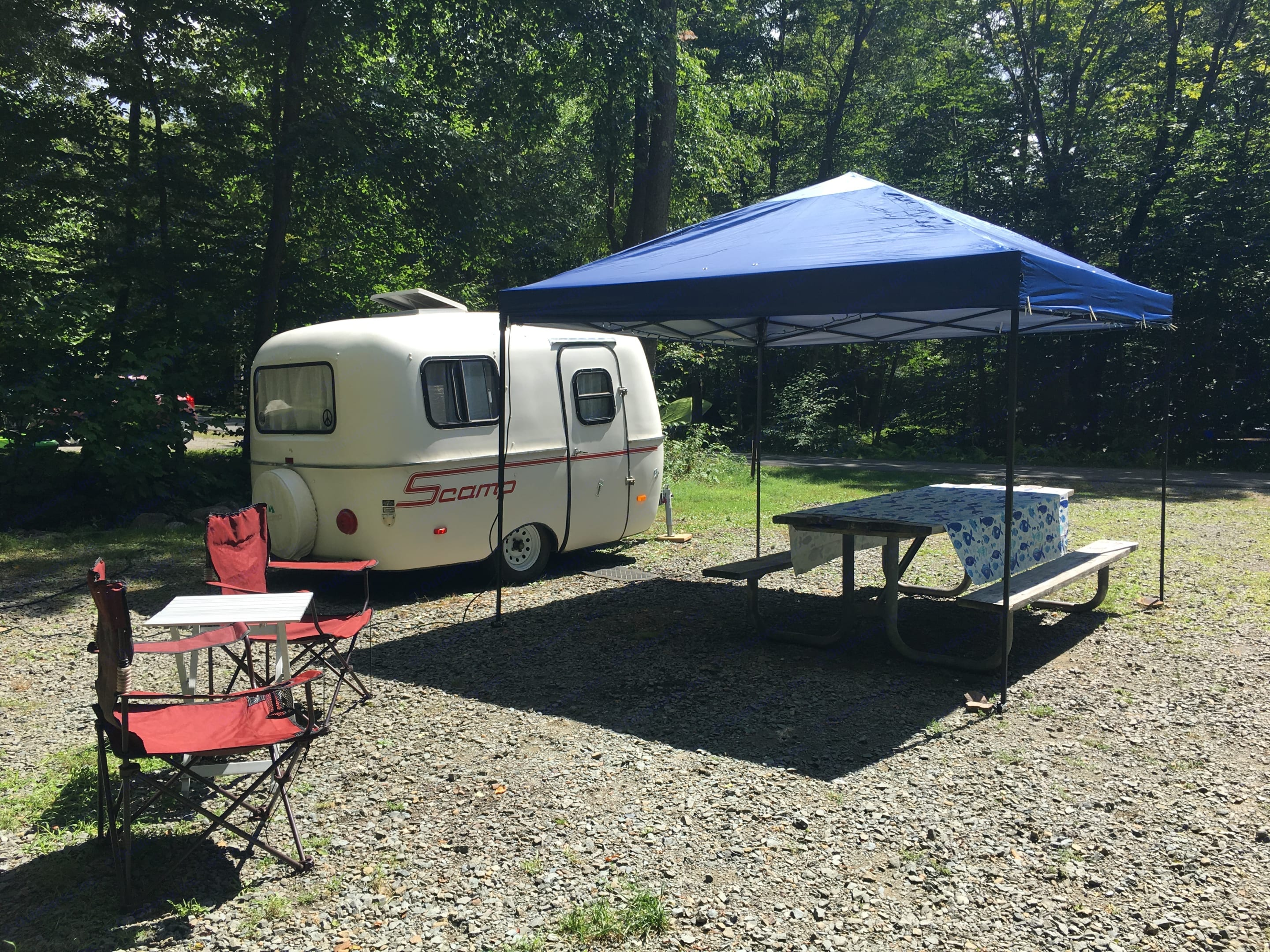 Scamp All American trailer with pop up tent, camp chairs and table cloth - all included in rental. Scamp 13' 1985