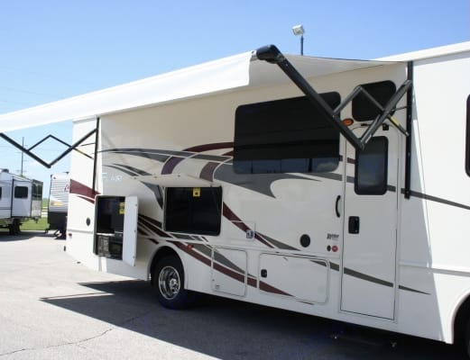 """This is a stock photo of the exterior area, Awning and kitchen area along with a 50"""" outside satellite TV. Fleetwood Flair 2021"""