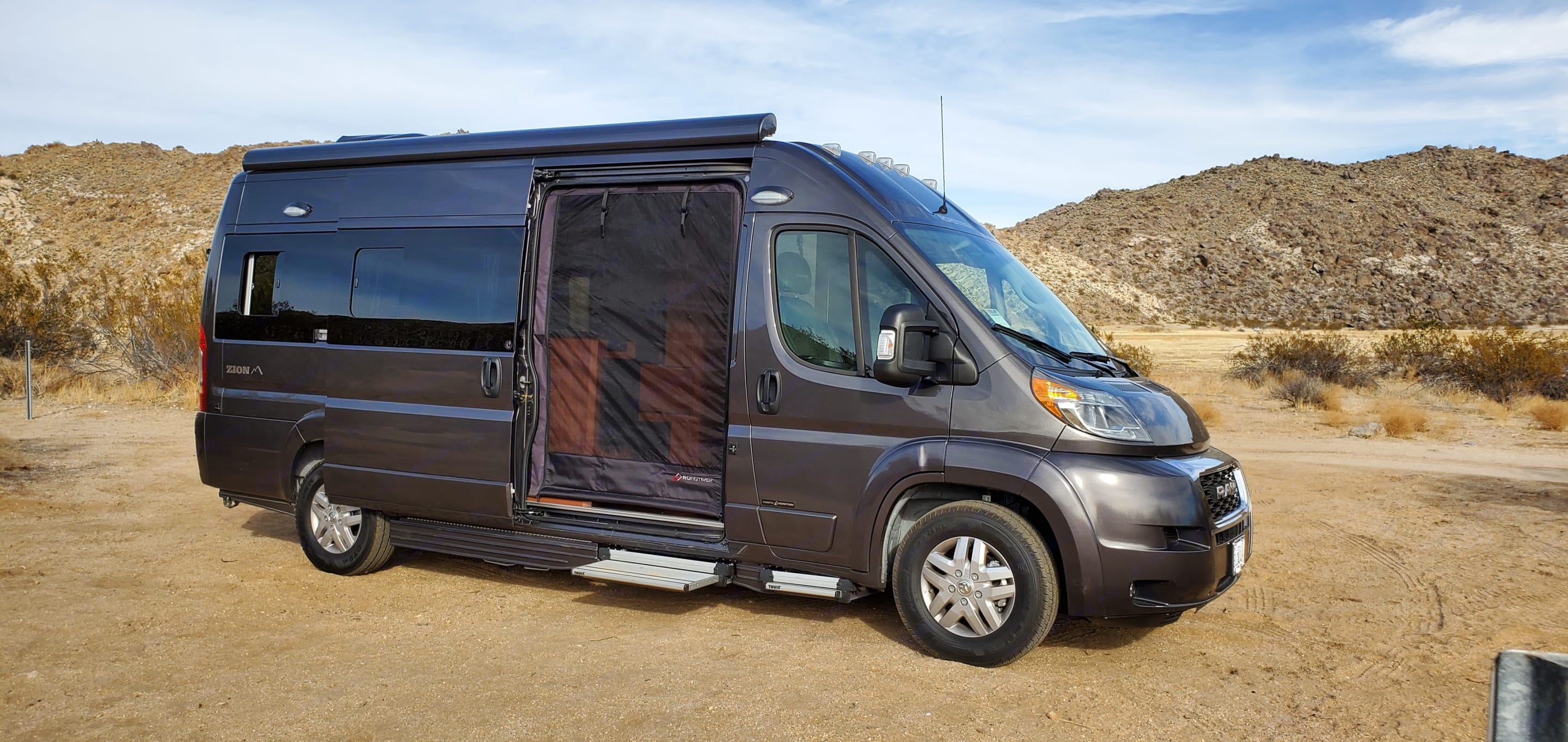 Mosquito screen down across coach door. There is an additional screen for the back doors.. Roadtrek Zion 2020