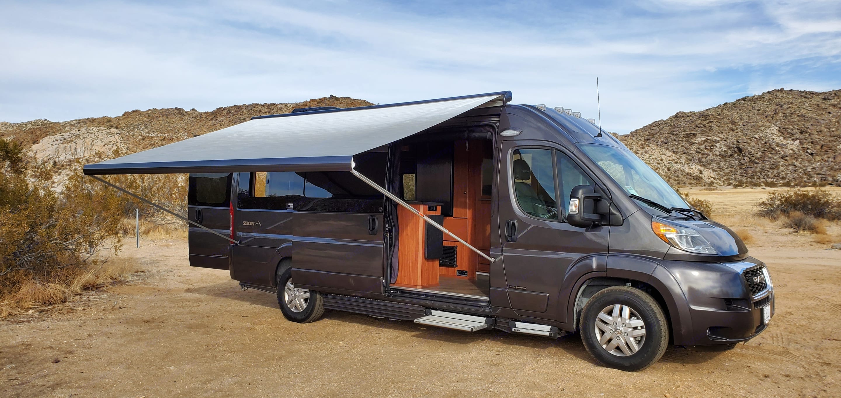 Awning fully extended with support bars in place; coach and back doors open.. Roadtrek Zion 2020