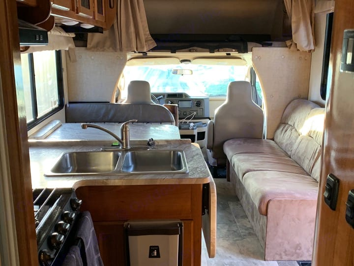 Efficient access from front to back. Sleeping area over the drivers cab. Climb up via ladder (not pictured). Storage above dinning table.. Coachmen Freelander 2019