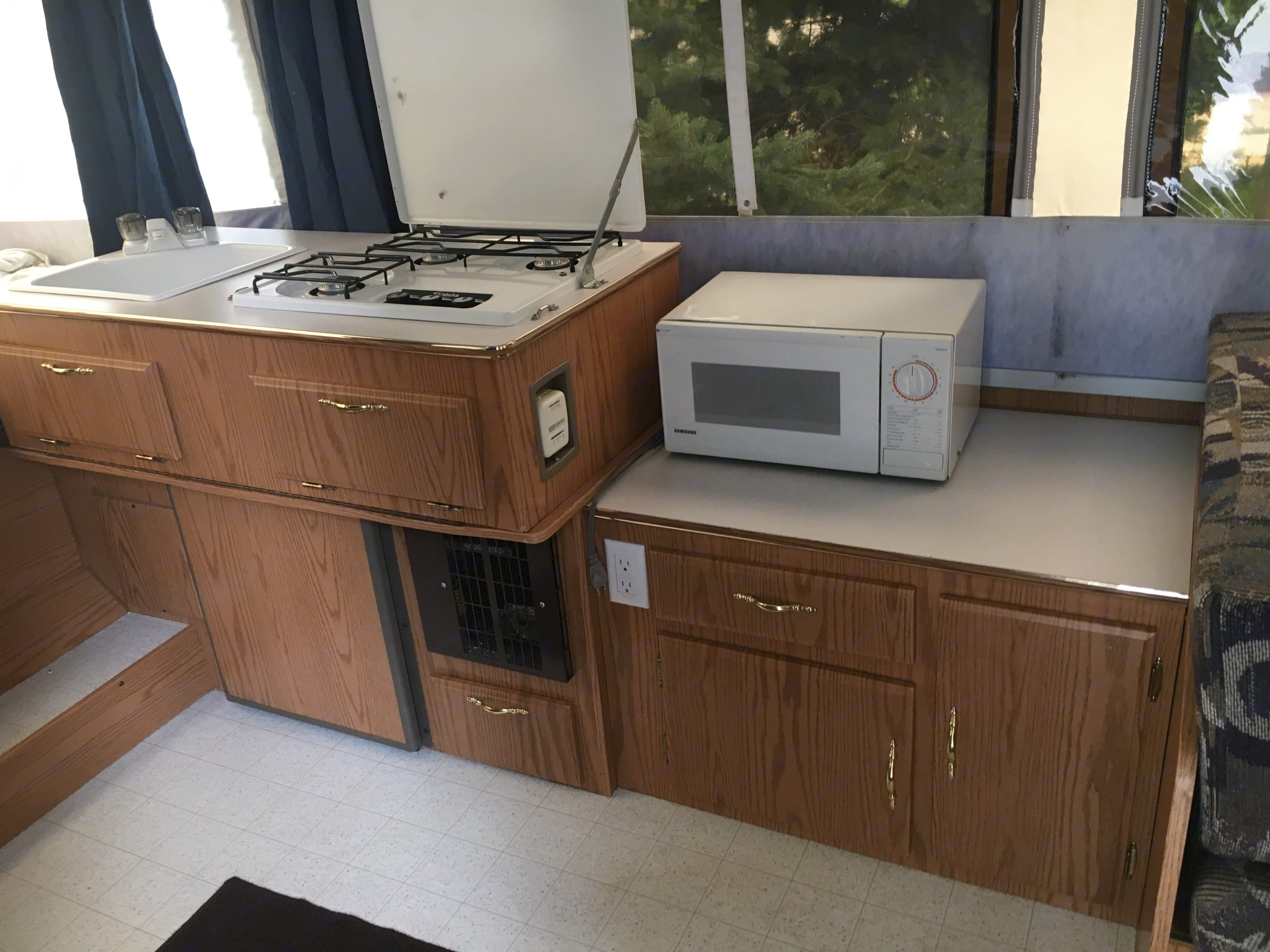 Single sink. Propane stove. Refrigerator. Mini microwave - must use exterior plug for use. Ample storage.. Forest River Rockwood 2004