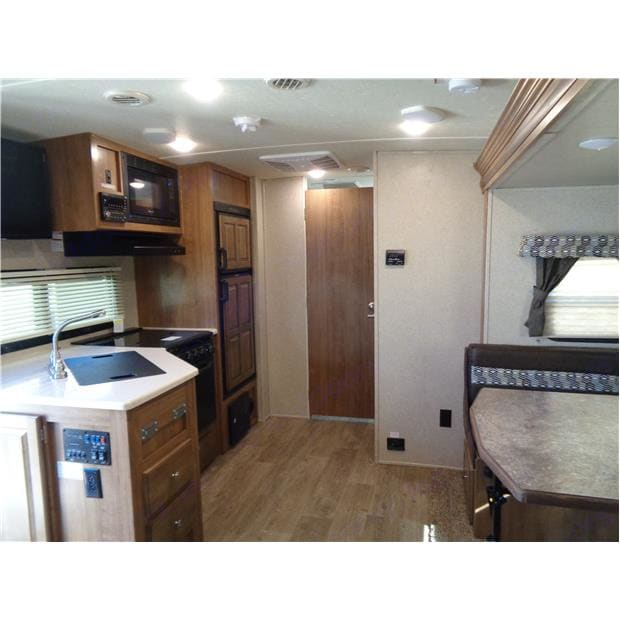 Kitchen includes a gas stove top, Oven, Dual Sink, Microwave, and Refrigerator.. Forest River Rockwood Mini Lite 2019