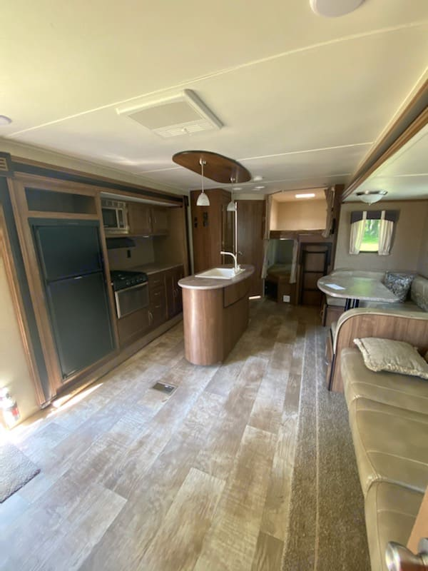Kitchen pops out to reveal an island w/ a sink. Kitchen also has microwave and stove w/ oven.. Gulf Stream Innsbruck 2018
