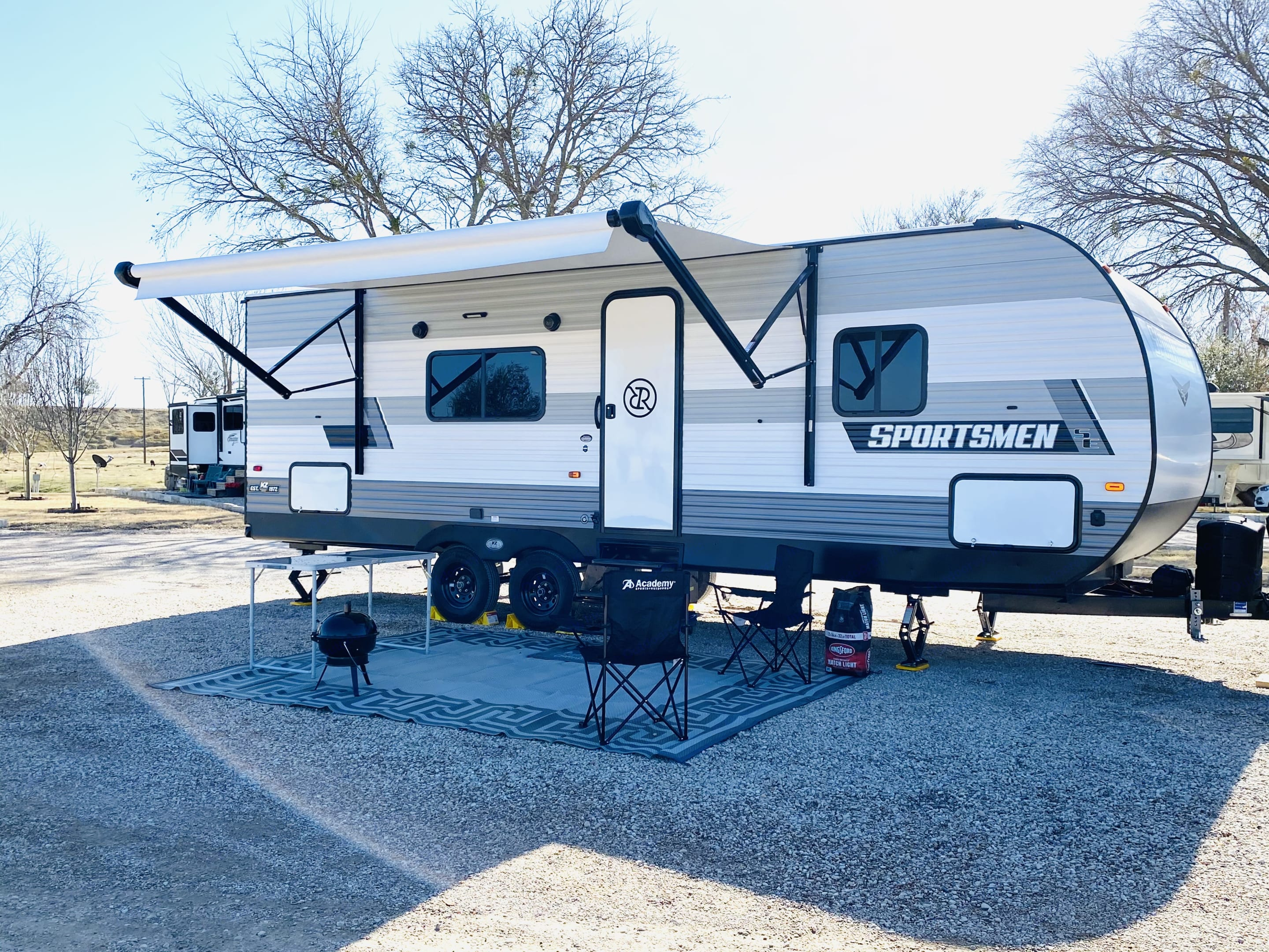 This is set up with the outdoor rug, table, chairs, BBQ pit. Its just missing you and your family.. K-Z Manufacturing Sportsmen 2021