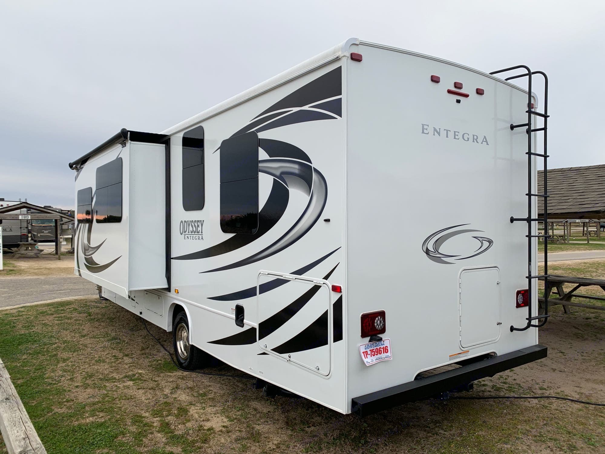 """Outdoor hot/cold shower and built-in water filter.  Slide out, dark tinted windows all around for privacy and temperature management. 4"""" steel rear bumper offers storage for drain tubes, away from your belongings!  Trailer hitch perfect for a bike rack, or tow capacity of 7500 lbs!. Entegra Coach Odyssey 29K 2021"""