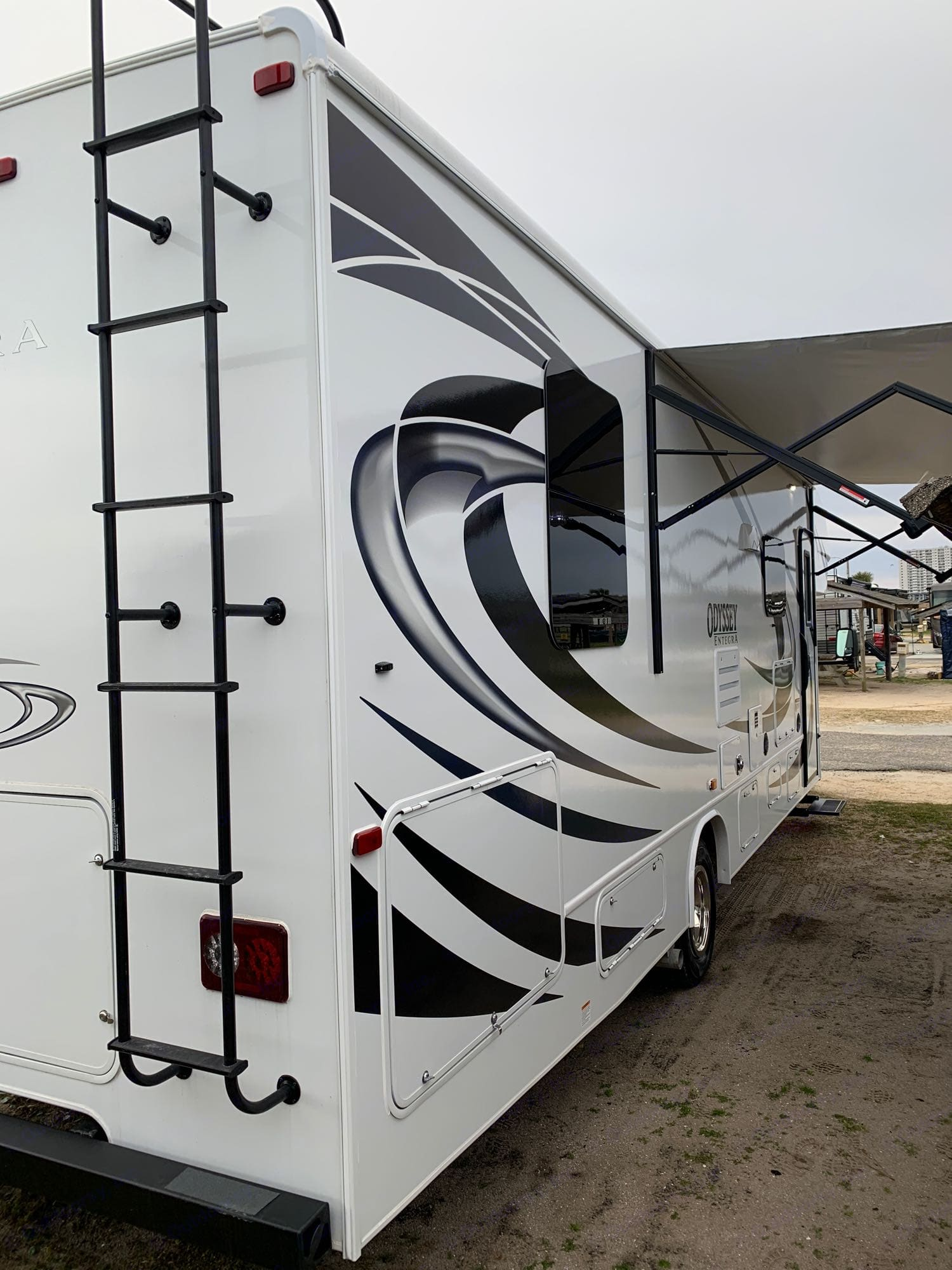 Tons of exterior storage and a view of the power awning with LED strip lights.. Entegra Coach Odyssey 29K 2021