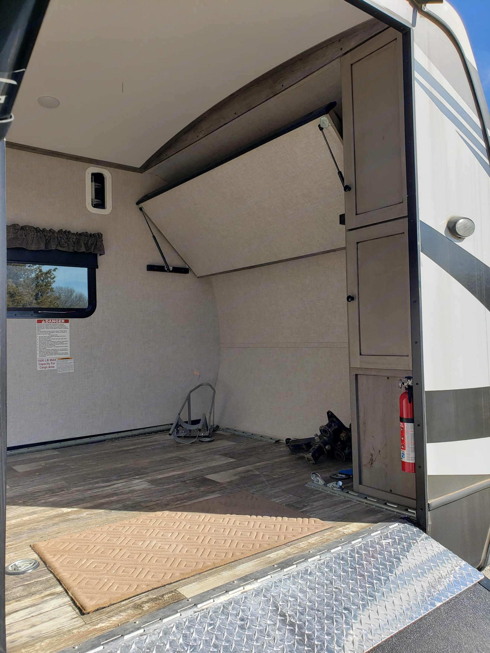 Wheel chock in the back corner for your Harley. Pull down storage shelf and a corner storage cabinet.  E-rail tie down system to secure your load. . Keystone Outback 2019