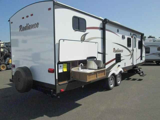 Exterior Pop Out Kitchen includes 2 burner propane stove (with connectivity to camper propane tanks), mini fridge, and sink. . Cruiser Rv Corp Radiance 2015
