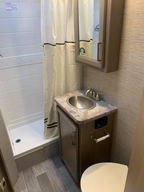 Private bathroom with shower, sink, and toilet, medicine cabinet, locked door. Thor Motor Coach Chateau 2021