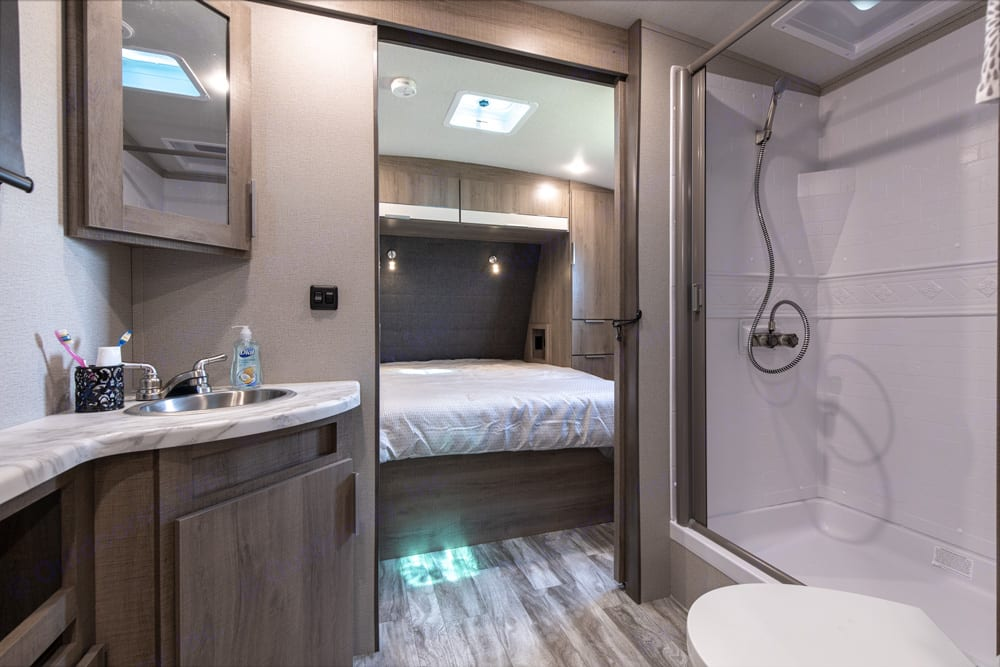 looking forward through the bathroom to the private bedroom. Grand Design Imagine 2910BH 2021